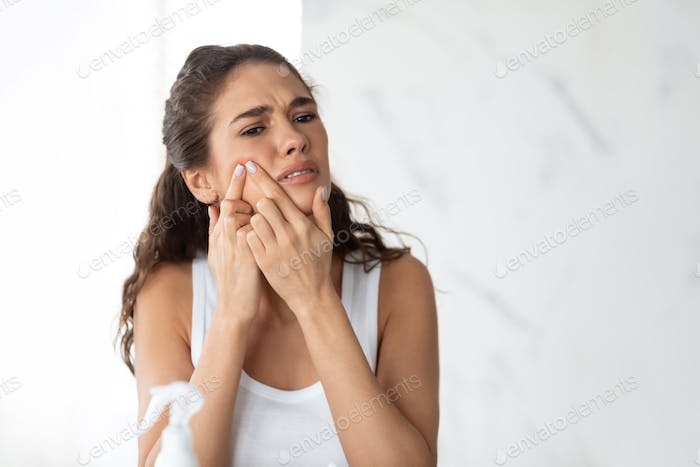Frustrated Lady With Acne Problem Squeezing Pimple On Cheek Indoor