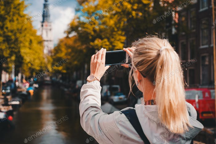 Woman tourist taking a picture of canal in Amsterdam on the mobile phone. Warm gold afternoon