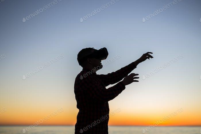 Junger Mann trägt Virtual-Reality-Schutzbrille auf Himmel Hintergrund Träume werden wahr