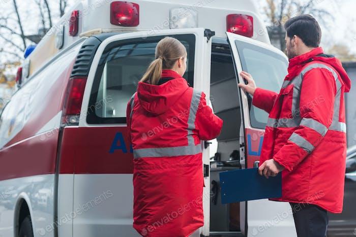 male and female paramedics closing ambulance doors