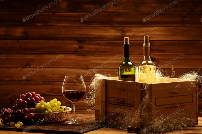 Bottles of red and white wine, glass and grape on a wooden inter
