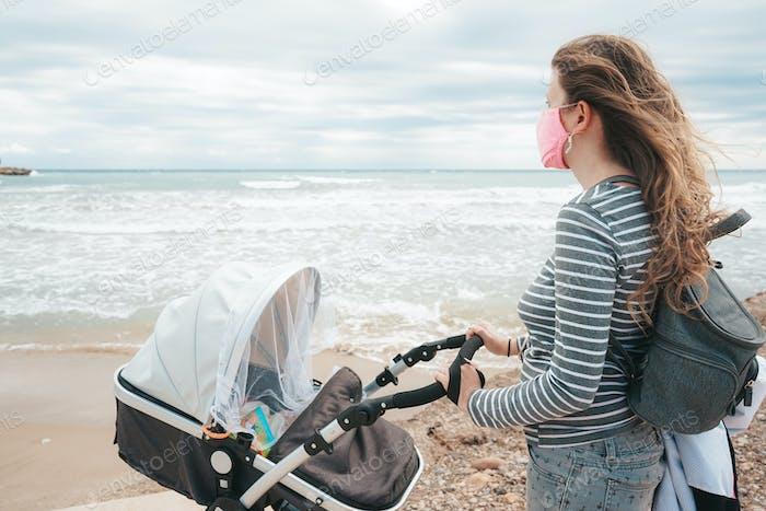 Junge Mutter zu Fuß mit ihrem Baby während kovid Pandemie
