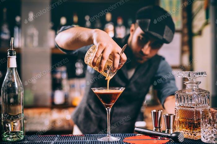 Vintage portrait of bartender creating cocktails at bar. Close up of alcoholic beverage preparation