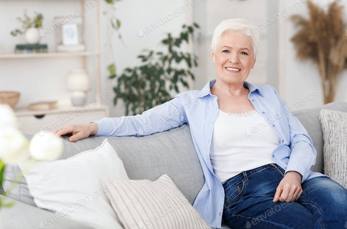 Smiling Elderly Lady Posing On Couch In Living Room At Home