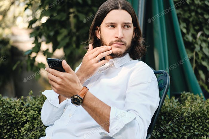 Young confident brunette bearded man in shirt with cellphone thoughtfully looking away outdoor