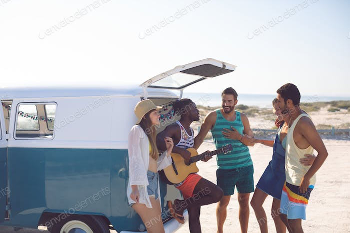 Side view of happy group of diverse friends having fun together near camper van at beach
