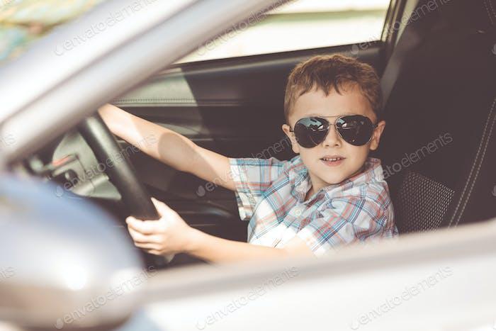 Ein glücklicher kleiner Junge sitzt im Auto.