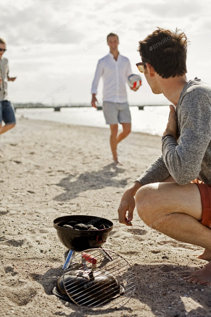 Young man barbecuing while looking at friends on beach