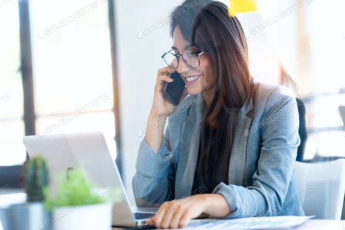 Smiling businesswoman talking on mobile phone while working with her laptop in the office.