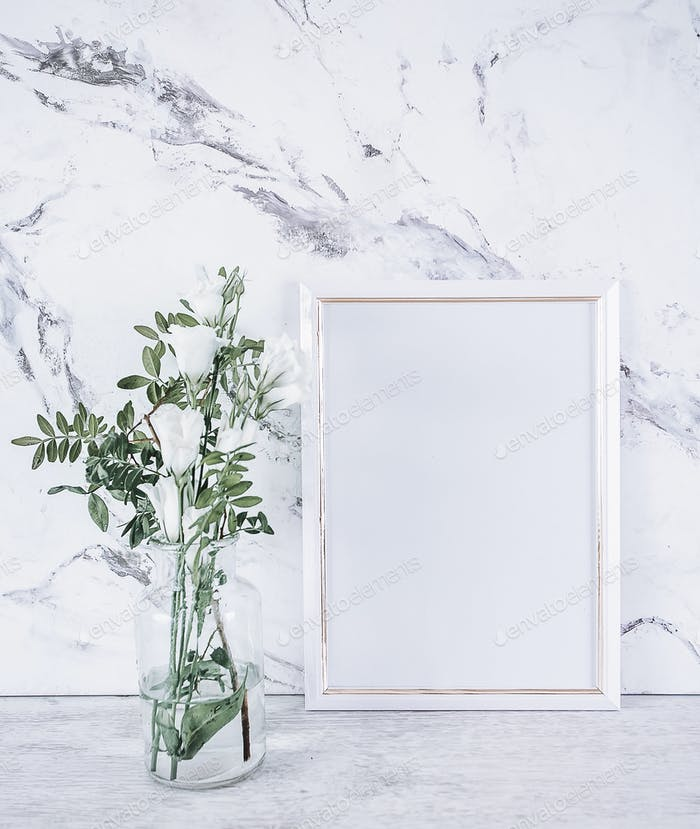 Blank frame and white flowers over marble table
