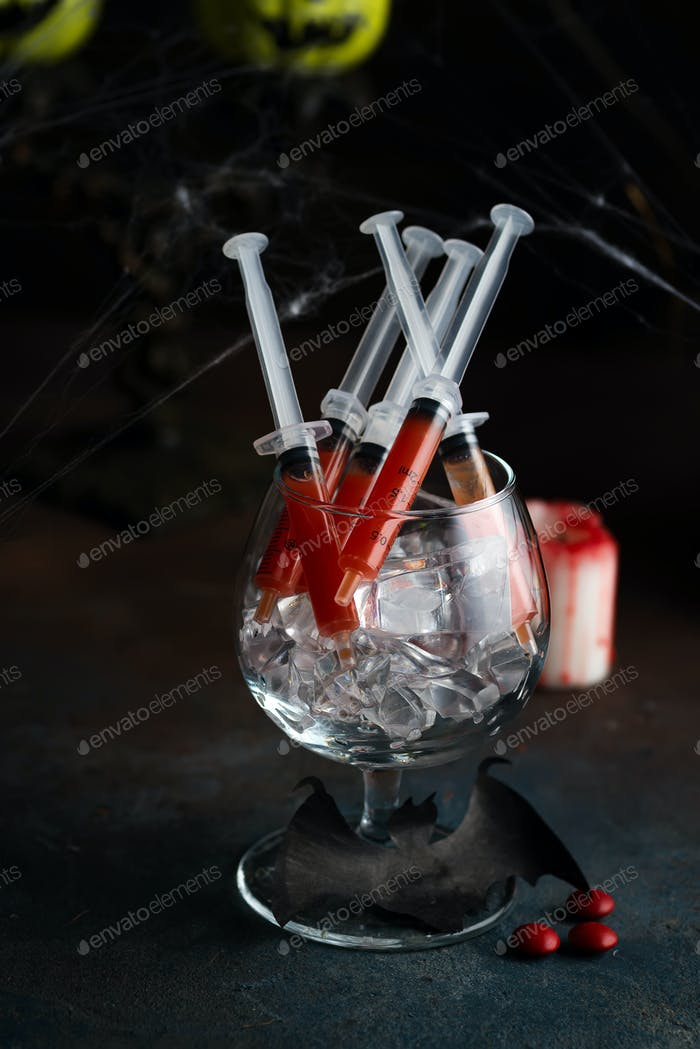 Bloody Mary cocktail in syringe with web for Halloween party celebration. Black stone background