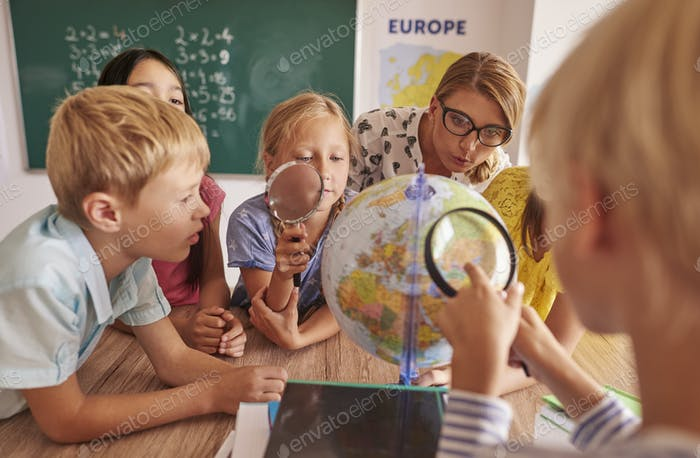 Children discovering new places in globe