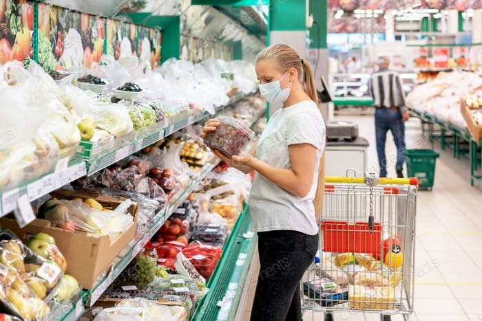 A masked woman during a pandemic is shopping at the supermarket.