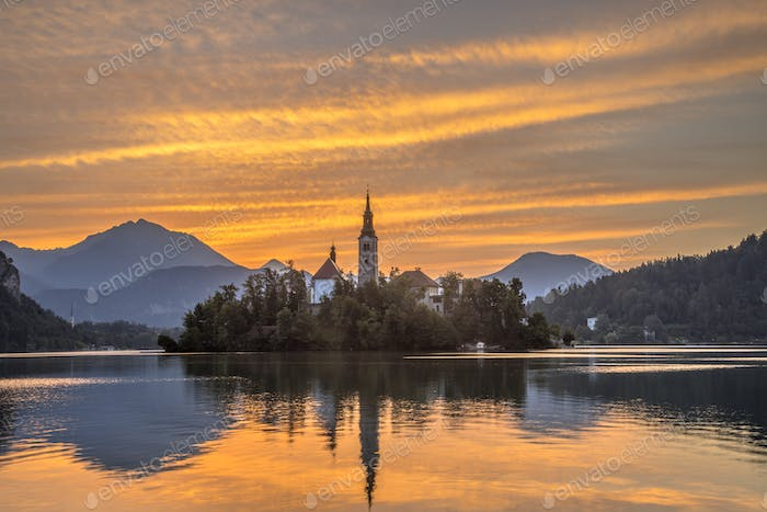Scenic Lake bled with church under orange morning sky