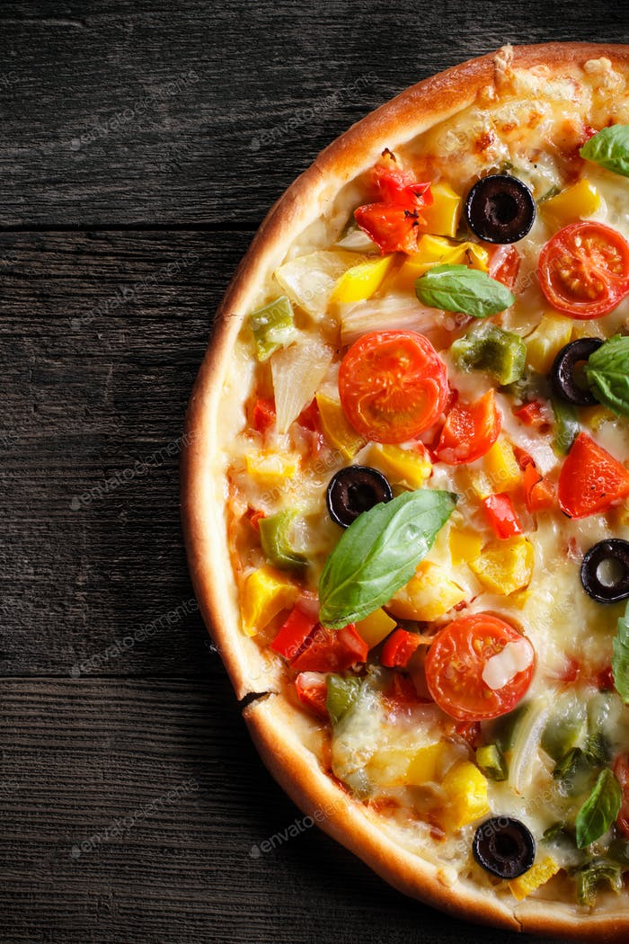 Pizza with salami and vegetables on an old wooden background.