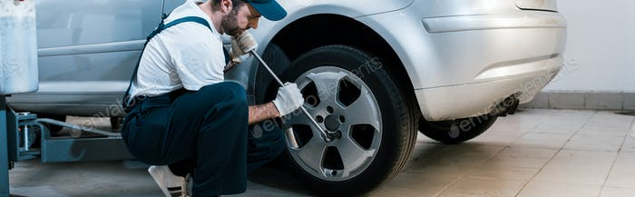 panoramic shot of handsome bearded car mechanic in uniform changing car tire in car service
