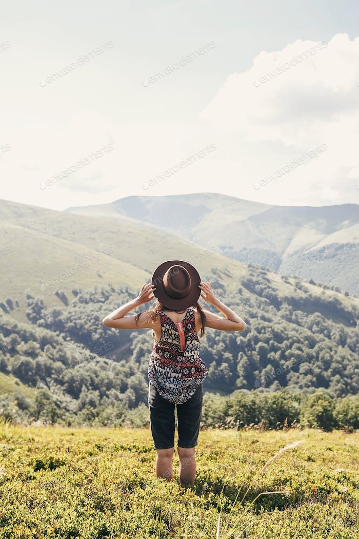 Traveler hipster girl in hat, walking in sunny mountains