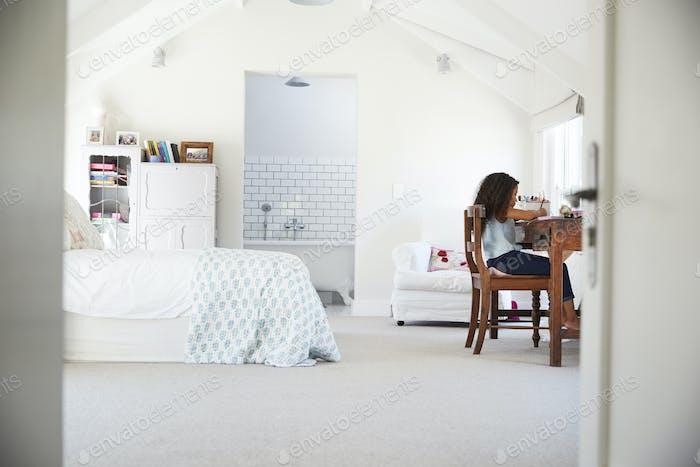 Young black girl sitting at desk, doing homework in her room