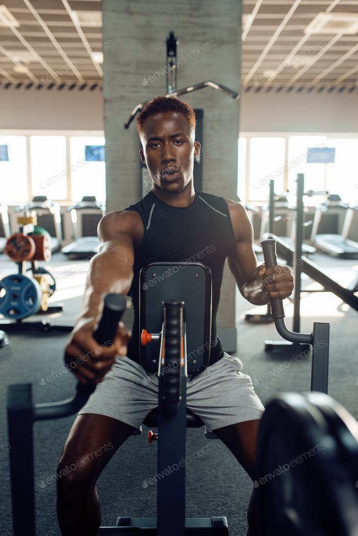 Muscular sportsman at exercise machine in gym