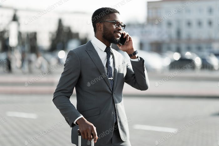 Calling Taxi at Airport. Businessman Talking on Phone