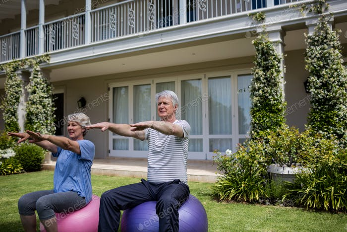 Senior couple exercising on fitness ball