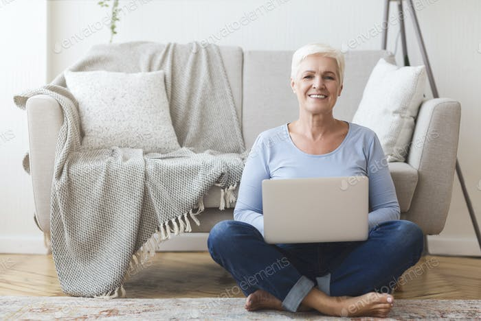 Active old woman sitting on floor and using laptop
