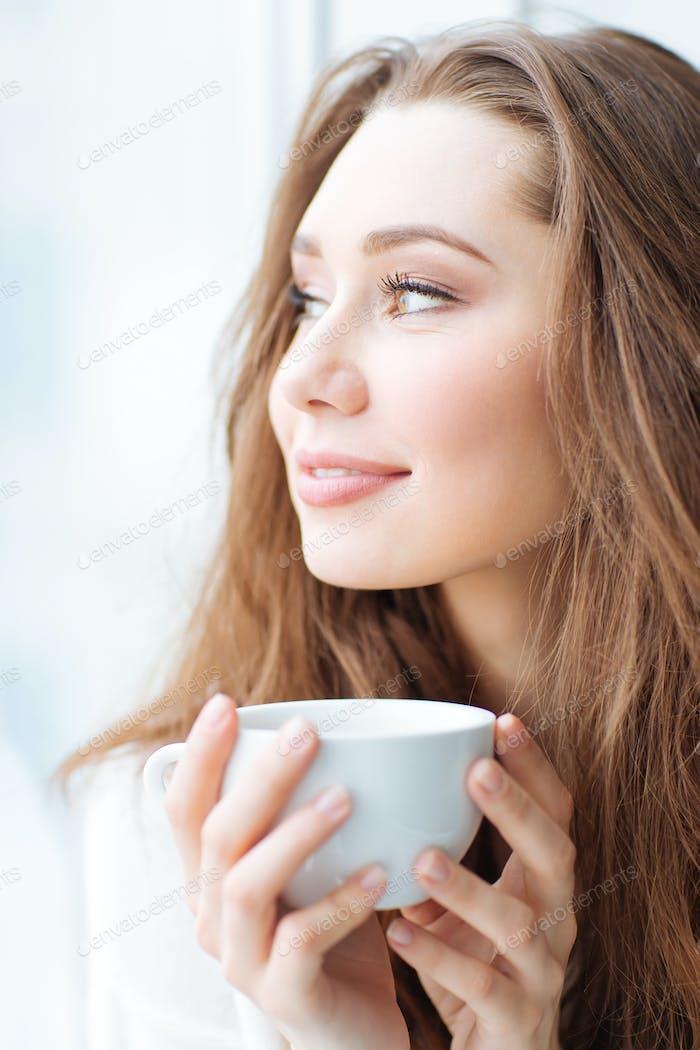 Charming happy woman drinking coffe
