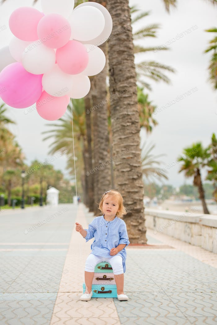 Happy little girl holding a bunch of balloons