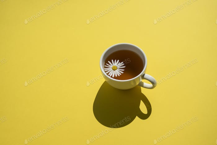 Cup of herbal chamomile tea on yellow