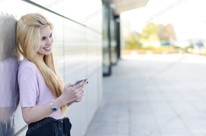 happy blonde young woman outdoor using her mobile phone