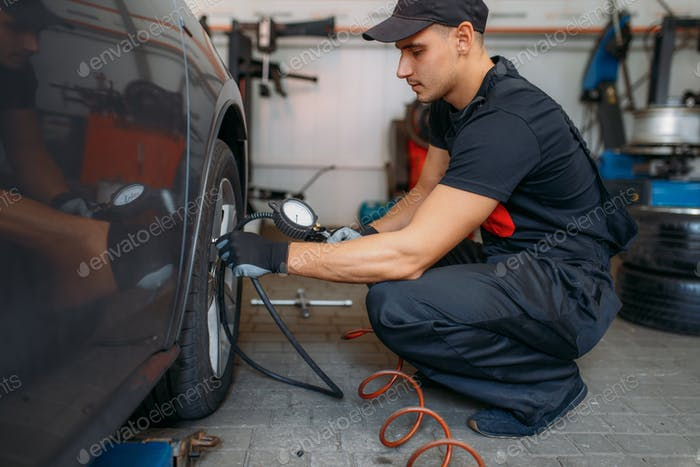 Auto mechanic checks the tire pressure in service