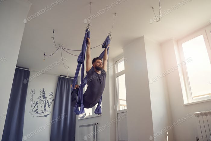 Hombre atlético barbudo practicando yoga antigravedad en estudio