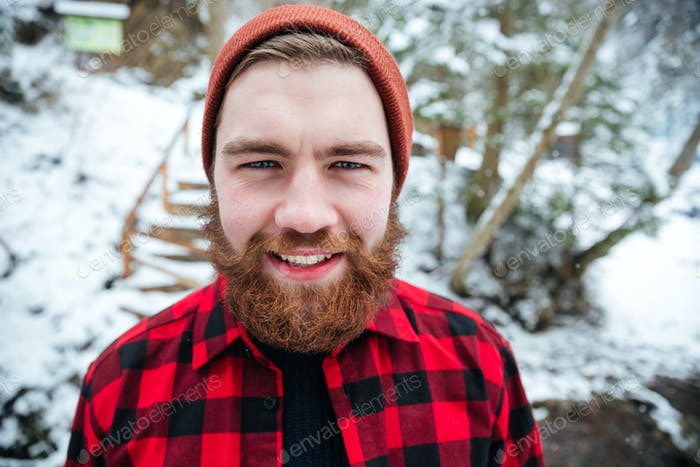 Cheerful bearded young man in winter forest