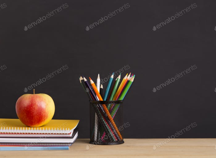 Apple, pencils and notebooks ready for using