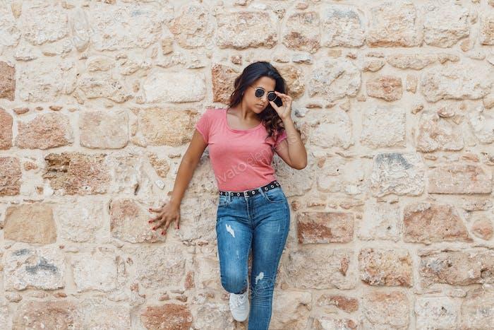 Placeit- Junge Frauen tragen T-Shirt und Jeans bleibt in der Nähe einer Wand