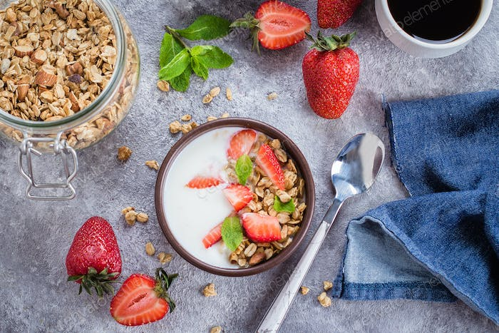 Flat-lay Food Concept. Yogurt, granola and strawberries on gray concrete table background