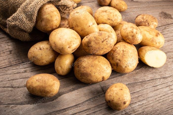 Neue Kartoffeln auf hölzernem Hintergrund