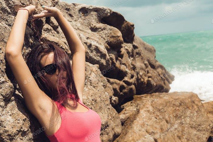 Sexy girl in pink t-shirt near bag rocks.