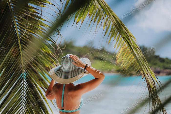 Woman on the beach in the palm trees shadow wearing blue hat. Luxury paradise recreation vacation