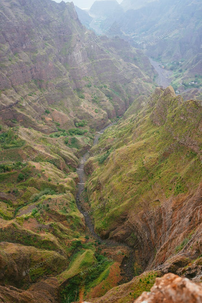Breathtaking view of canyon with steep cliff and winding riverbed with lush green vegetation on