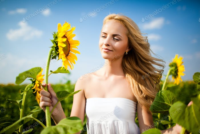 Girl looking at sunflower and smiling