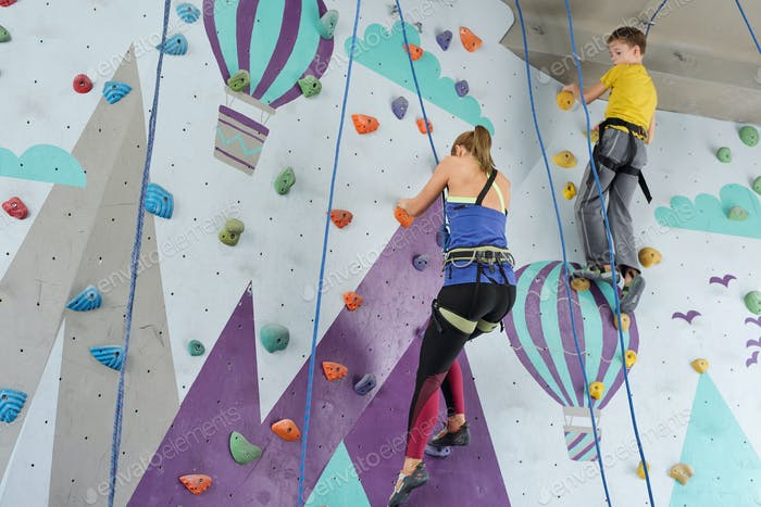 Blonde girl and schoolboy grabbing by small rocks on climbing equipment