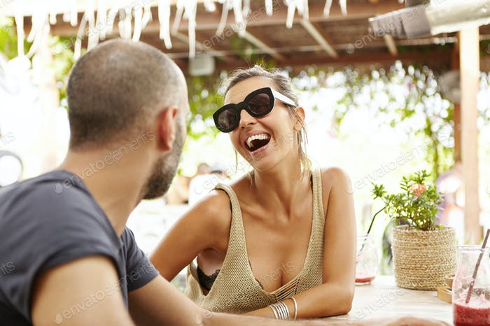 People and lifestyle concept. Outdoor shot of woman in stylish shades laughing at jokes of bearded m
