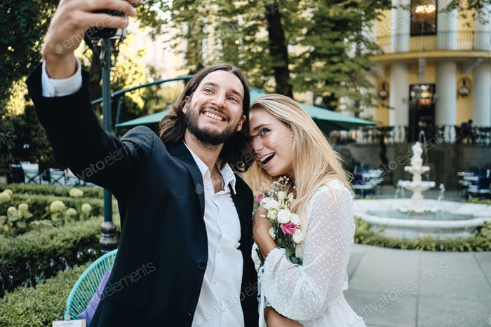Beautiful romantic newlyweds happily taking selfie on cellphone together in garden of restaurant