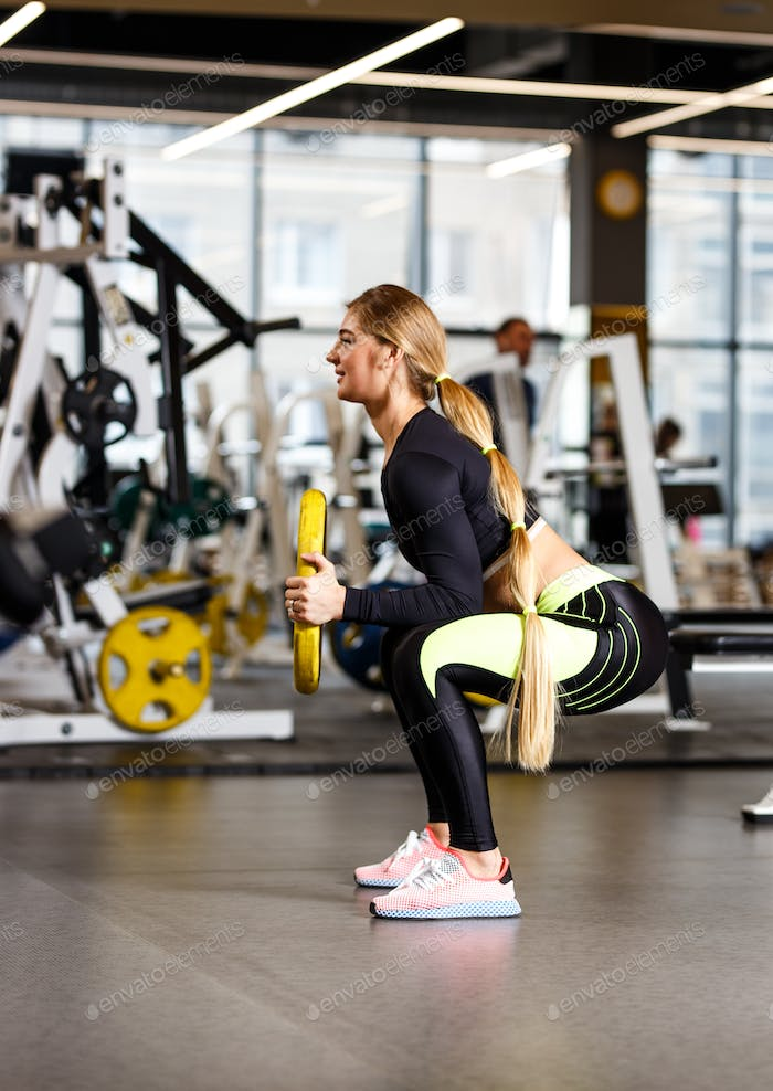 Slender girl with long blond hair dressed in sportswear is doing squats with plate in the modern gym