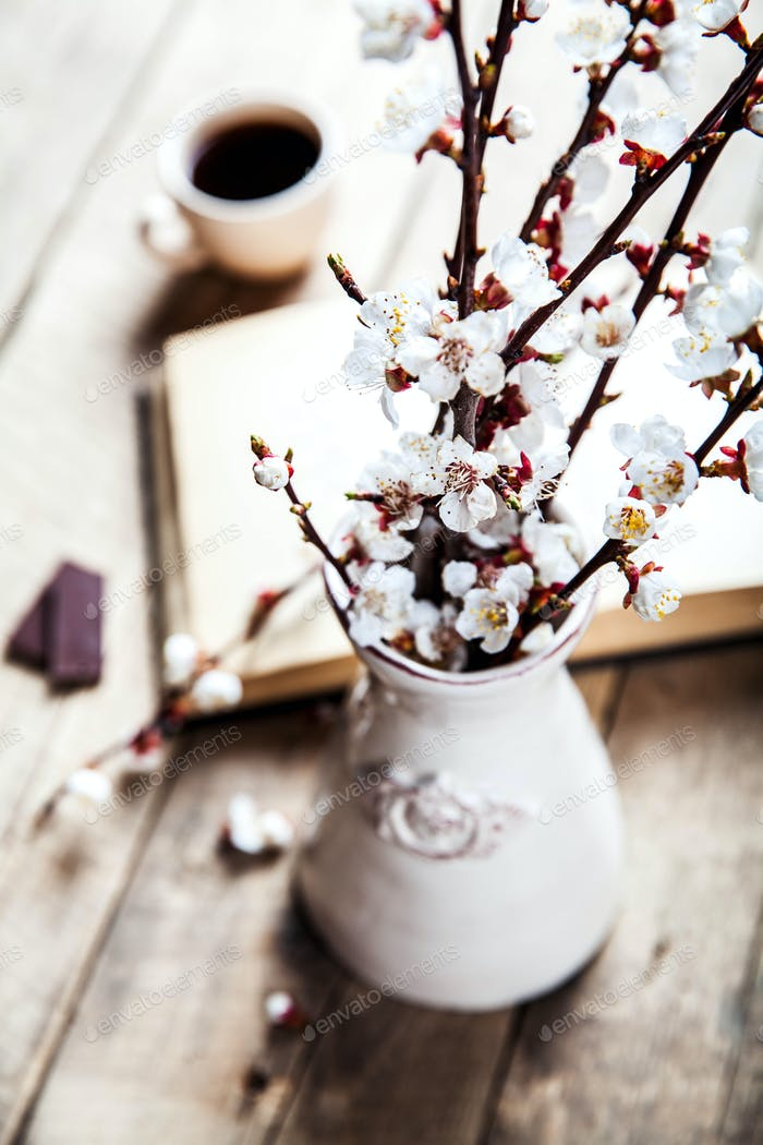 Open vintage book with blossom branch of cherry-tree on wooden table with a beautiful vintage vase