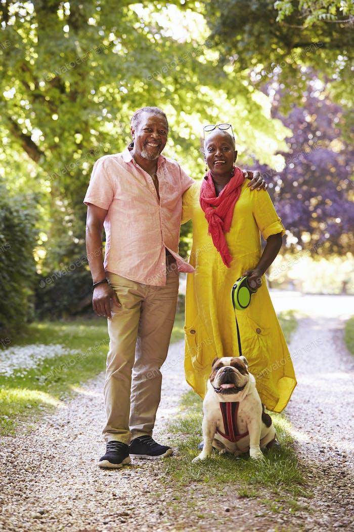 Portrait Of Senior Couple Walking Pet Bulldog In Countryside