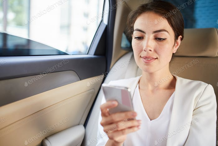 Young Woman Using Smartphone in Car