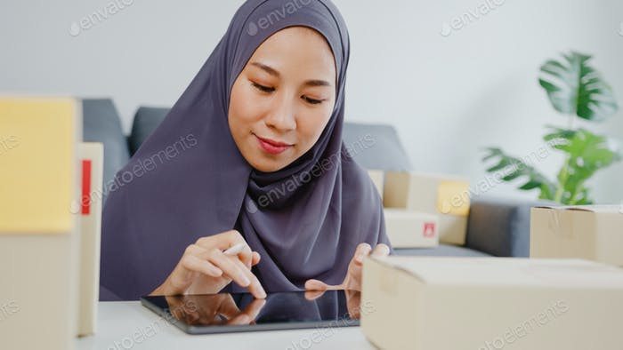 YYoung Asia muslim businesswoman check product purchase order on stock and save to tablet computer