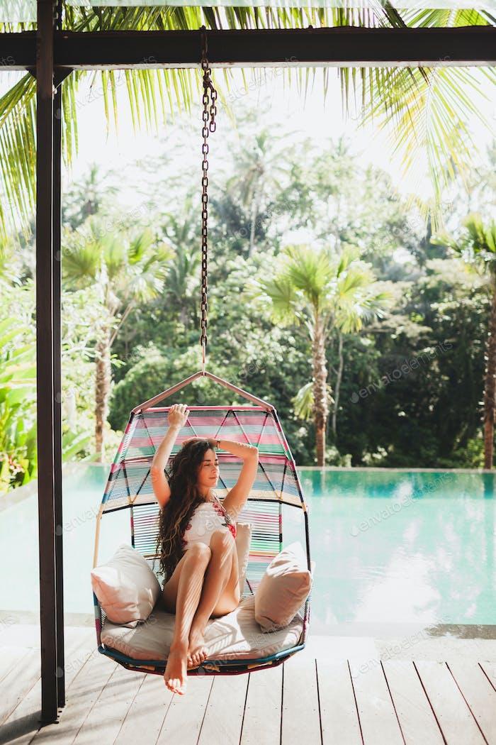 Woman in white swimsuit enjoying in hanging chair swing on poolside in luxury hotel.
